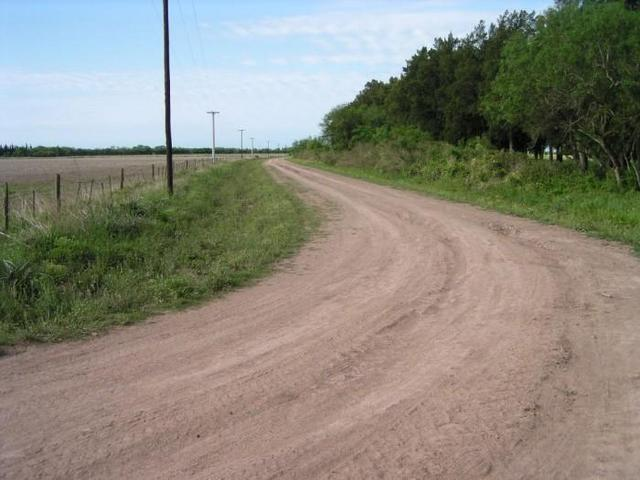 the dirt road parallel to the highway, seen towards North
