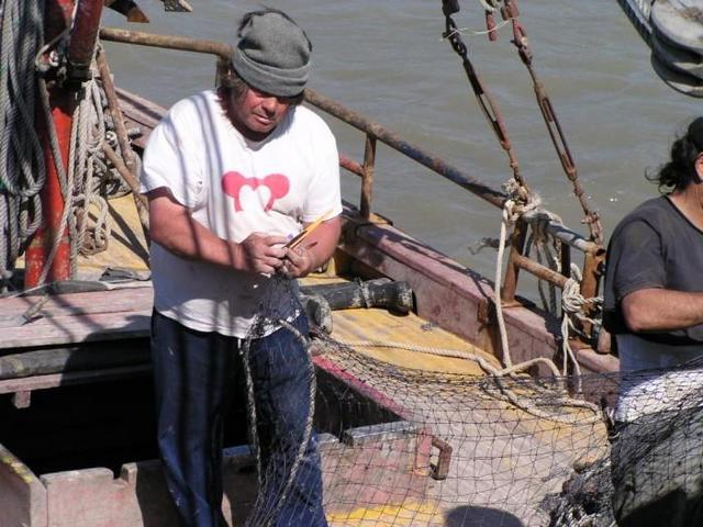 "repairing fishing nets on the ""Siempre Amabile"""