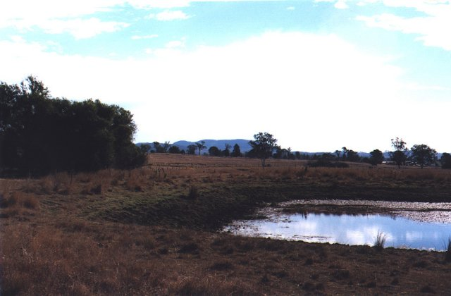 A slough to the east of the confluence, with mountains in the background.