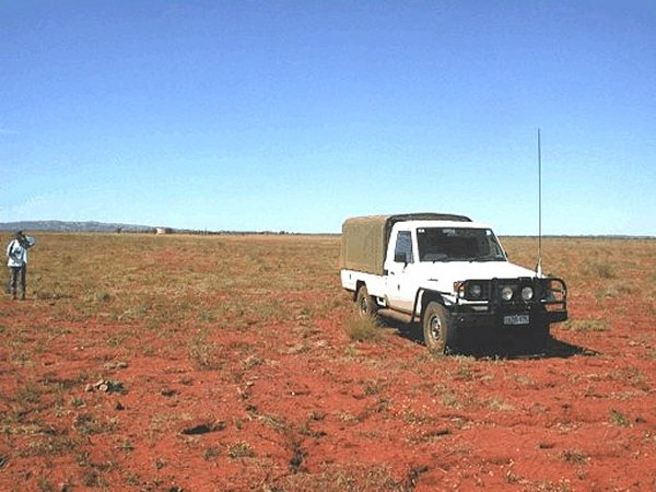 Our trusty 4WD and Robin standing at the confluence. Old cattle yards in the middle-distance.