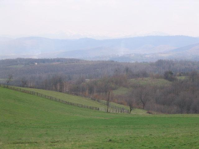 View south from the car: the confluence 180 m down the hill. Snow capped Mount Bjelašnica on the horizon.