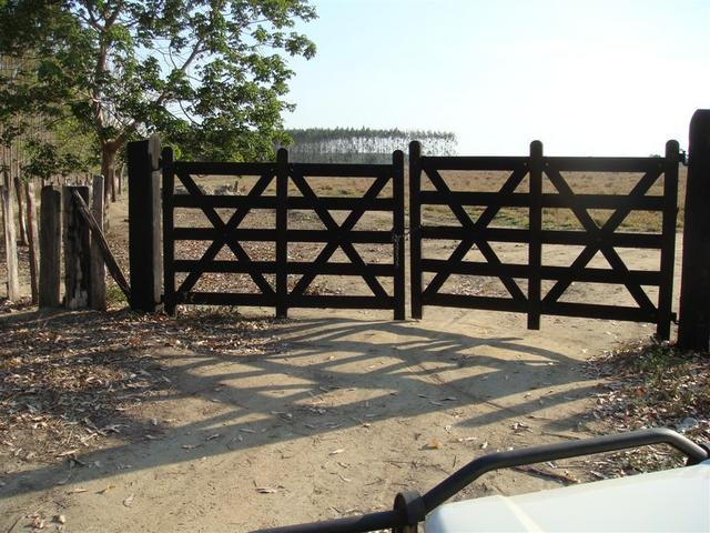 Porteira trancada. Gate closed with padlock.