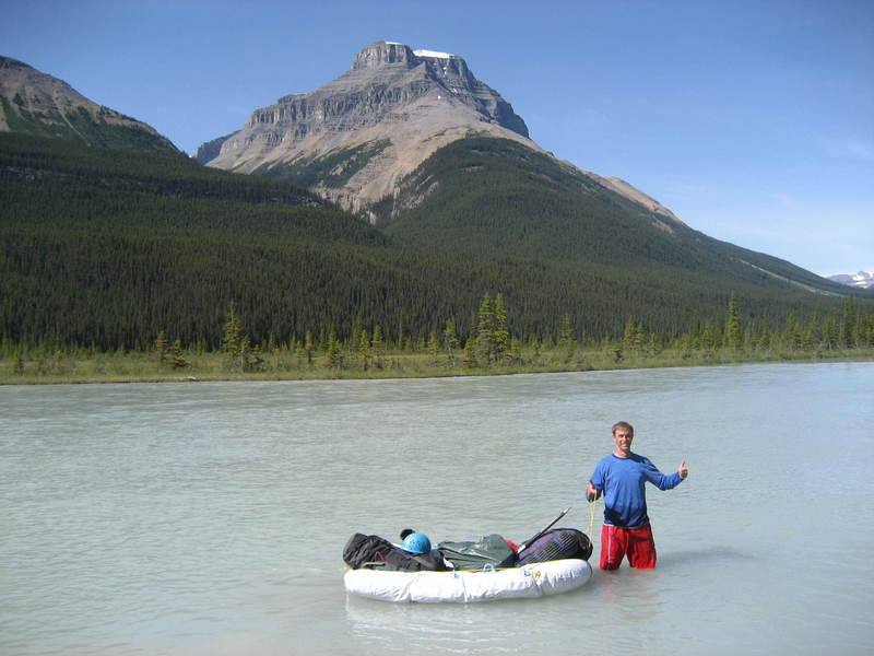 Chris using the dinghy to cross the North Saskatchewan river.  Notice the water marks up to his belly button level.