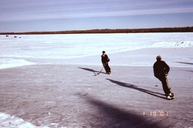 A father and son practice hockey on the lake.