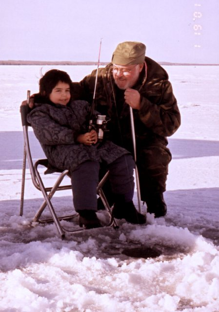 A girl and her grandfather, ice fishing.