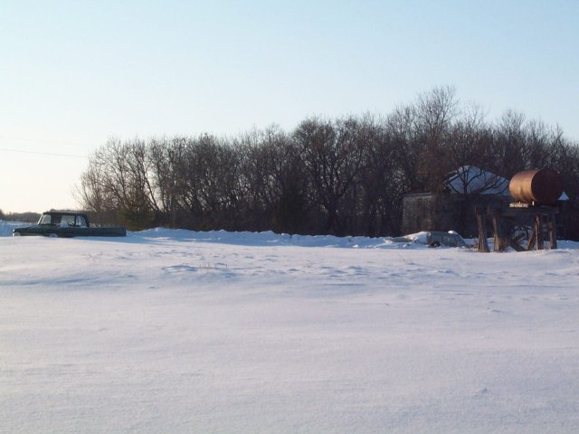 View to the West with House, Snow-Submerged Truck and Fuel Tank