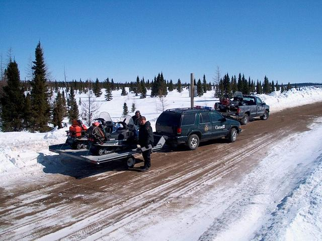 Loading snowmobiles near the bridge at MishwopTurn on South Feeder, Paradise River, Labrador.