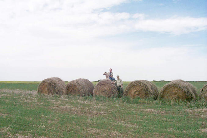Max, Carolyn and Alan posing on huge bales of hay just south of the confluence.