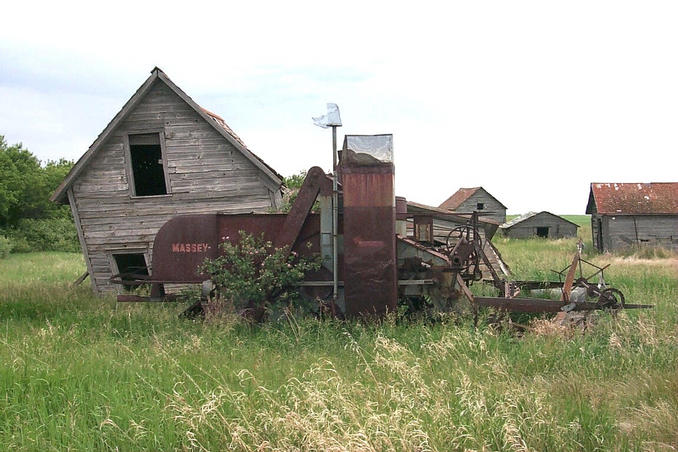 Outbuildings and machinery on the homestead. Note the wild roses growing around the machinery.
