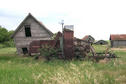 #9: Outbuildings and machinery on the homestead. Note the wild roses growing around the machinery.