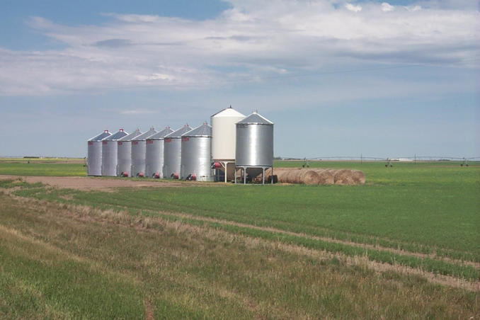 Grain bins and hay bales with sprinkler system in background.