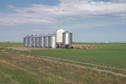 #8: Grain bins and hay bales with sprinkler system in background.