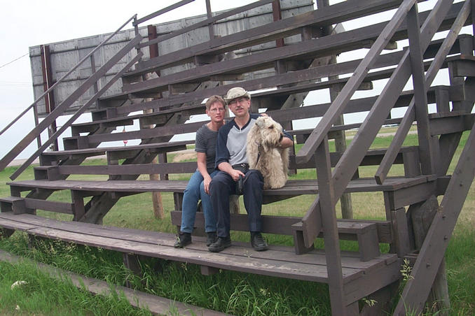 Carolyn, Alan and Max on the bleachers on the Vanscoy rodeo grounds.