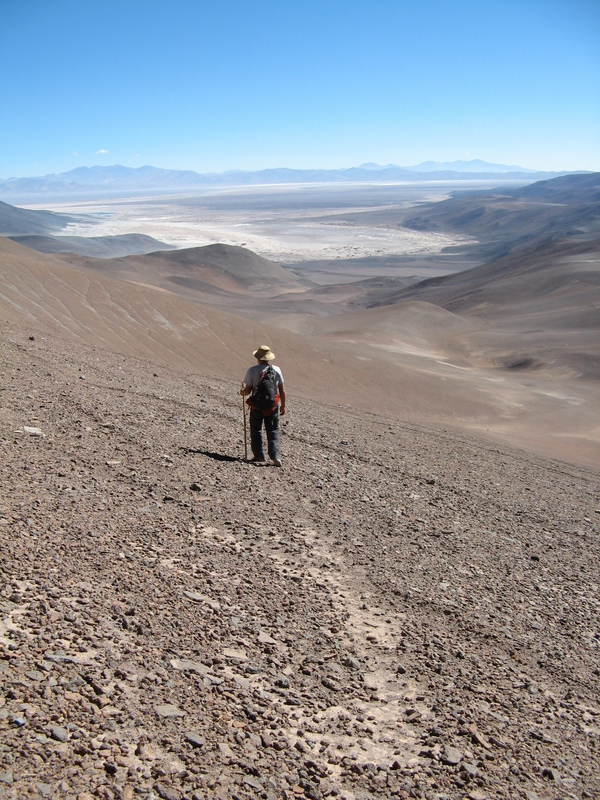 Sharky walking on Guanaco trail back to camp.  View of Salar Pedernales.