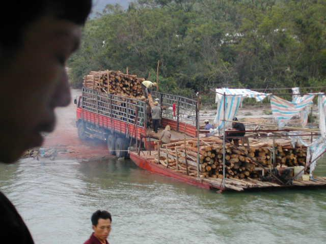 Log barge off loading onto a cargo truck
