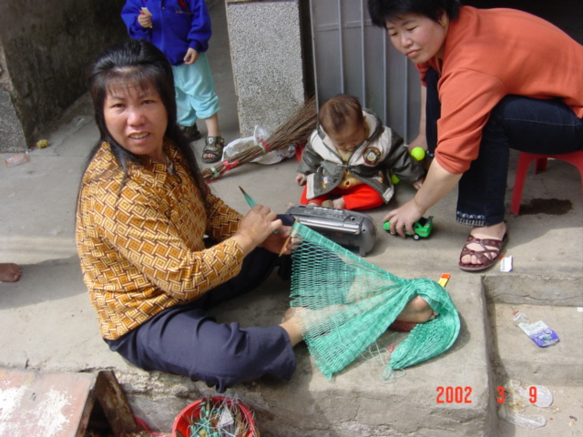 Womenfolk sitting outside their homes weaving nets