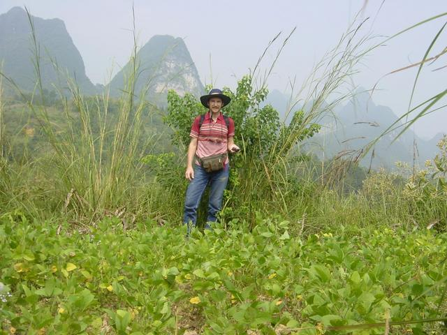 Targ standing on the confluence point, with huangdou (soya beans) in the foreground and karst mountains behind