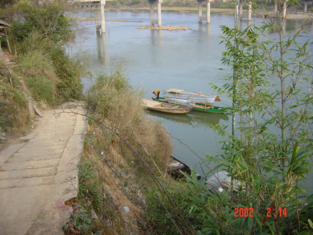 The boat serving as the only means of river crossing until the bridge in the background is completed