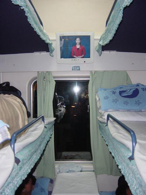 Modern hard-sleeper compartment on train from Shenzhen to Meizhou, with comfortable bunks and flat-panel video screen