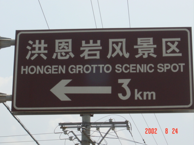 Large, bilingual sign, indicating the way to Hong'en Grotto Scenic Spot.