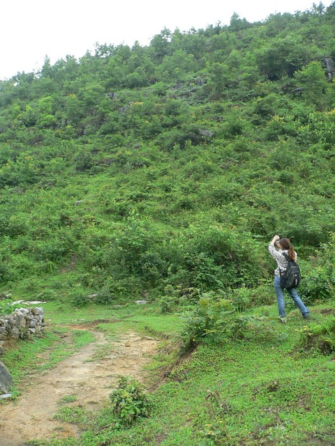 Ah Feng standing near the good path, taking a photo of the slope on which the confluence is located.