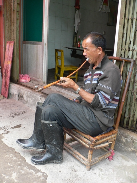 Man smoking a pipe on the roadside in Dàtáng.