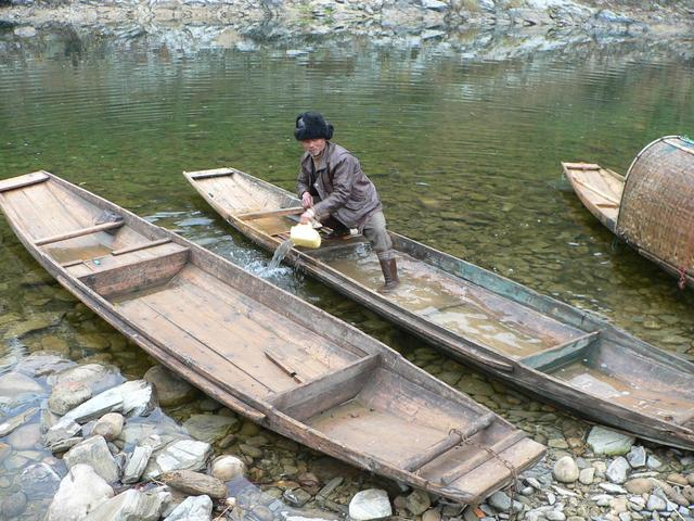 Fisherman bails out boat prior to taking us across Duliu River. (What's wrong with the other two boats?)