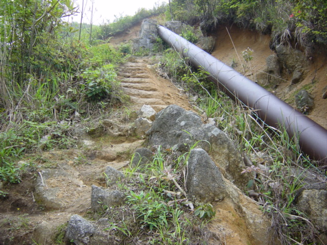 Pipe channelling water to the power plant below, with steep path running up beside it