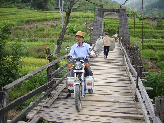 Village chief on motorbike crossing suspension bridge over Wenjiang River