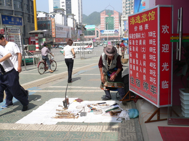 Man selling animal parts on a street in Zūnyì.