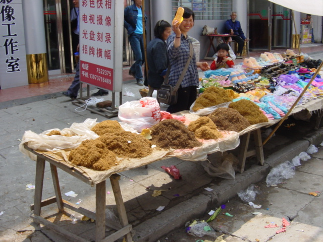 Plastic shoe stall alongside a tobacco stall in Pingkou