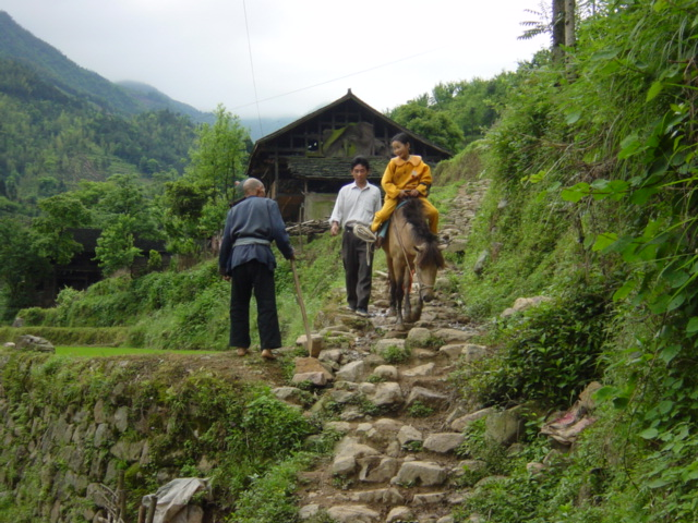 Young girl on horseback, making her way down a stone path into Tielu from somewhere in the surrounding countryside