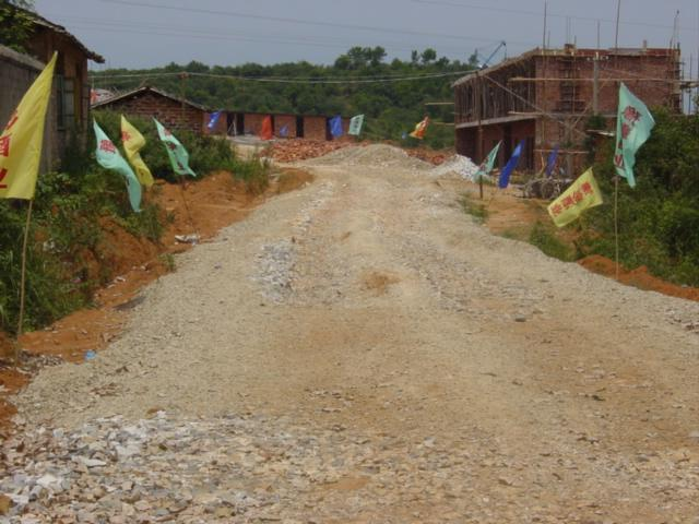 Gravel road to construction site, with confluence on top of hill behind