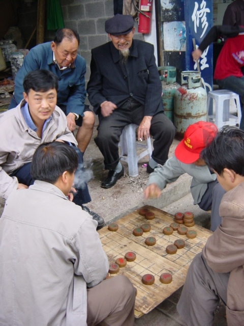 Action scene from the ubiquitous pavement Chinese chess match