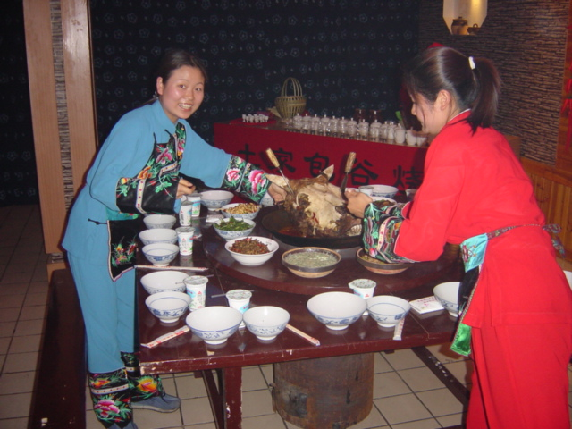 Girls dressed in traditional Tujia minority nationality dress placing a large wok containing a bull's head at the centre of the table