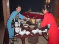 #3: Girls dressed in traditional Tujia minority nationality dress placing a large wok containing a bull's head at the centre of the table