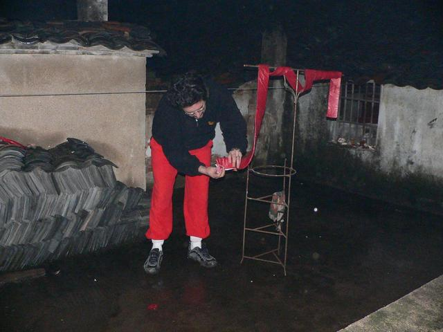 Tony setting off firecrackers at midnight on the roof in the rain