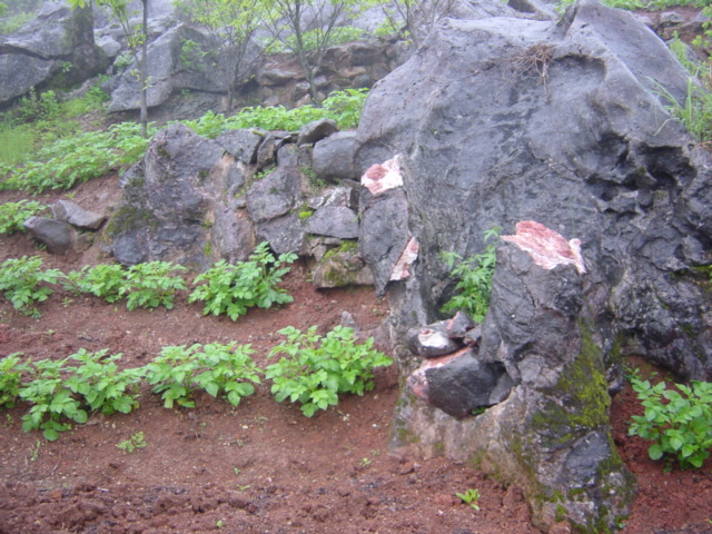 Large boulders, black on the outside, red and white on the inside