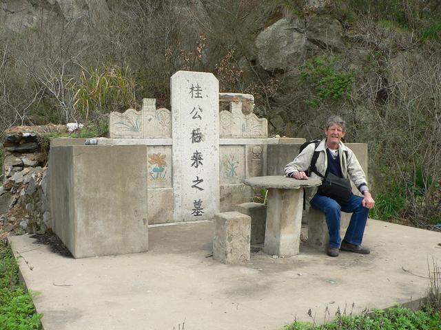 Jim sitting at the picnic table in front of a Chinese grave