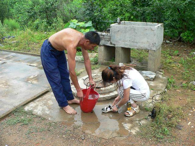 Local assists Ah Feng to clean mud from shoes and feet.