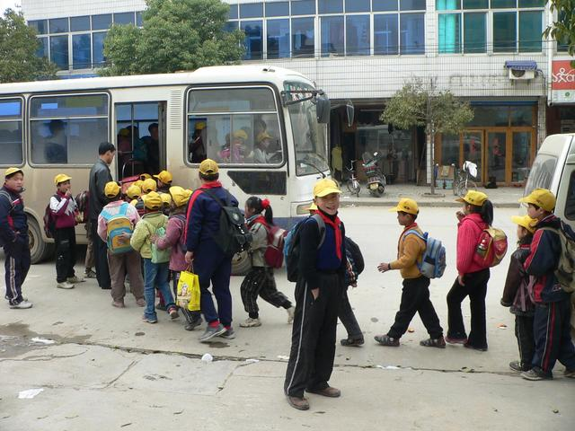 Schoolchildren queuing up to board bus in Hongqiao