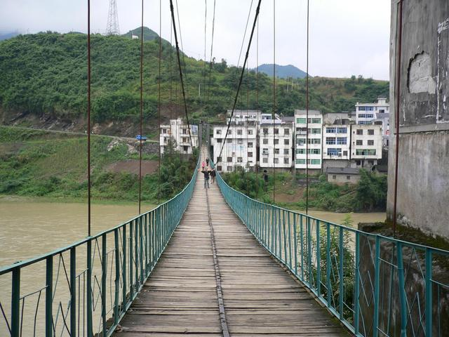 Targ on pedestrian suspension bridge with Guandu behind.
