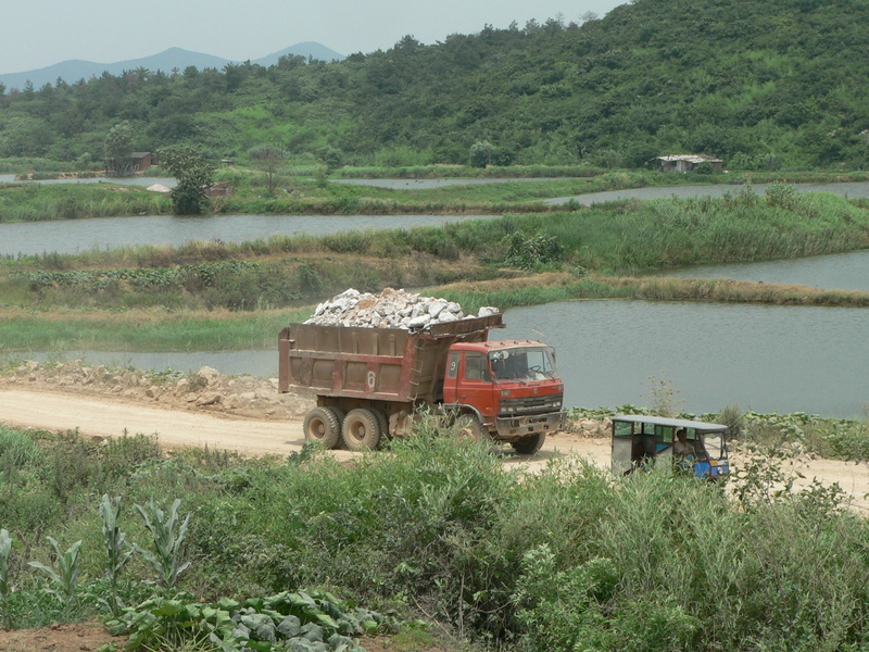 A truck loaded with rocks rumbles past our waiting three-wheeler
