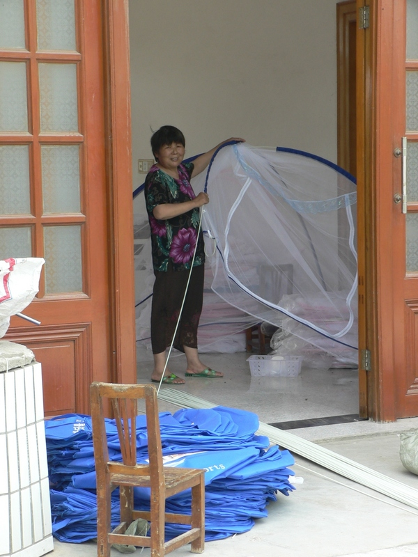 Local resident making mosquito nets in her home