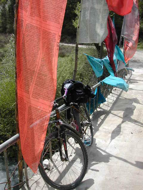 My bike and Tibetan Prayer Flags at a bridge