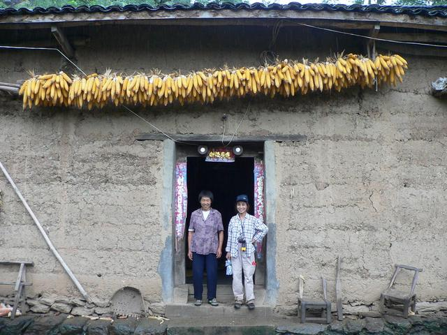 Ah Feng and nice lady in doorway of her home.