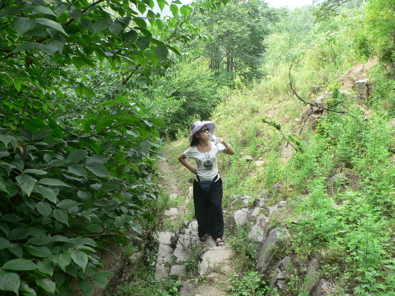 Ah Feng pauses for a sip of water on the path up into the hills