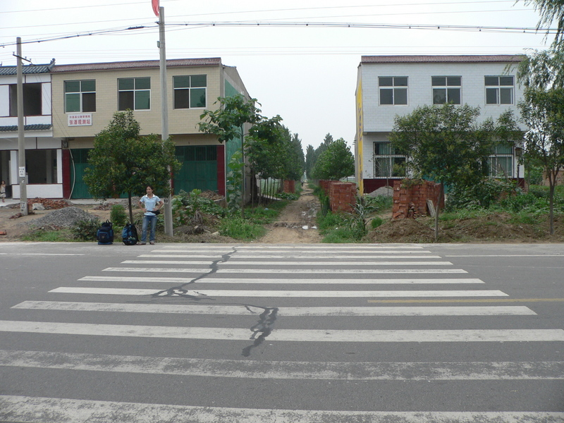 Ah Feng at the pedestrian crossing 460 m south of the confluence, which marks the beginning of a small dirt road, nestled between two houses