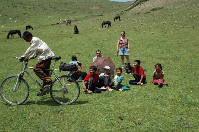 The waiting party and the Yak herders with one of them trying out the mountain bike