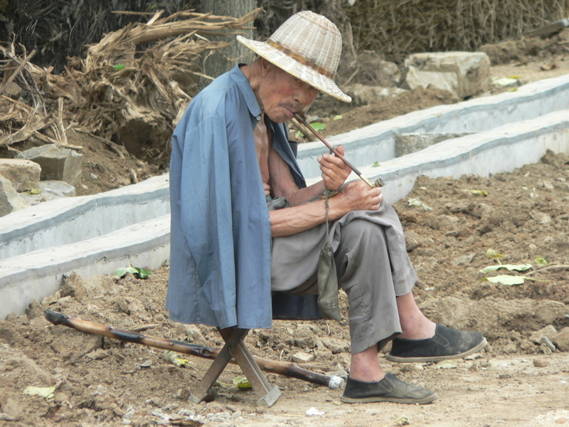 Old man smoking a long pipe